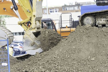 Excavator bucket clearing sand soil at construction site Stock fotó