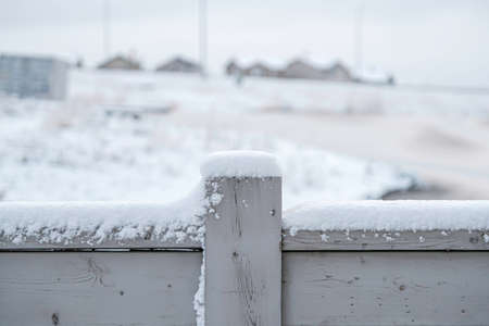 Snow on fence and fence post on a street