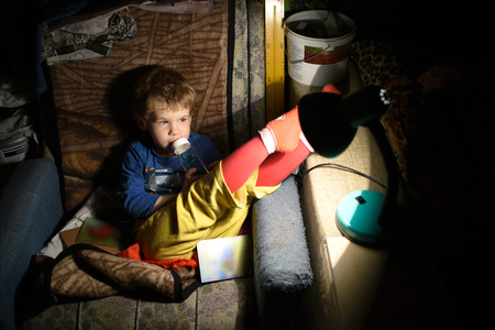 untidiness: Child Eats. Child Sitting On a Chair In a Dark Room In Front Of The Lamp And Eats Stock Photo