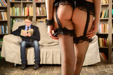 adult sex: The sexy girl`s Booty in black lingerie in front of young man who is reading a book. The sexy girl  in black lingerie going to young man in library. Stock Photo