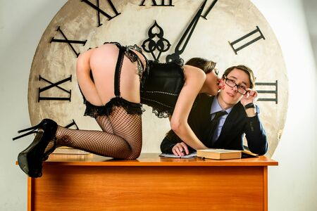 sex education: Bad Teacher. sexy teacher is seducing to her student who is redding. sexy girl is seducing a man who is reading on a desk. A sexy female teacher and her student in front of the big clock