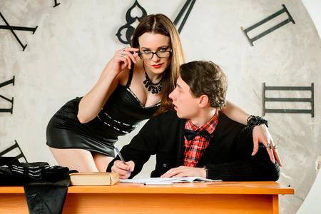 tetas: Mal Profesor. Profesor atractivo est� seduciendo a su estudiante que est� escribiendo. sexy chica est� seduciendo a un hombre que est� escribiendo. Un profesor de mujer sexy y su estudiante frente al gran reloj