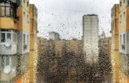 dirty: water drops against gray spring sky with buildings, focus sat at the in front of. Rain on The dirty Window.
