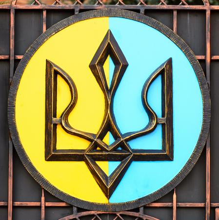 emblem of ukraine: Painted Coat of arms of Ukraine is on a black iron. National Emblem of Ukraine Painted Iron. Close-up Stock Photo