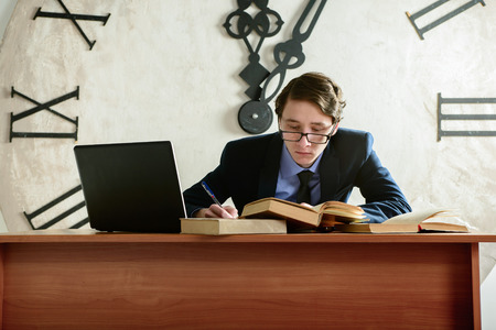 medium shot: Man is studying and take notes late at night. Concentrated student studying at his desk in front of The biggest clock. MLS. Medium Shot Stock Photo
