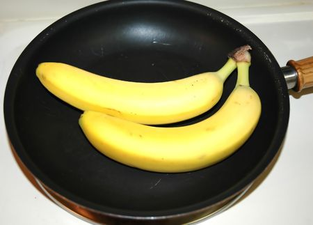 Bananas in a frying pan on a stove top. Stock Photo