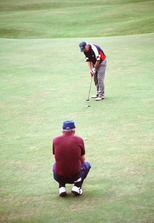 greens: Two men playing a round of golf on the greens.