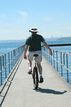 Unicyclist riding on the pier. photo