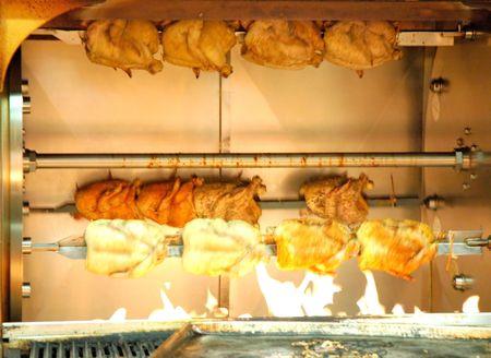 pollo rostizado: Un comercial asador lleno de pollos cocinados.