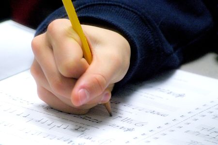 person writing: Student writing music in class. Stock Photo
