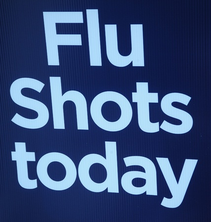 Flu shots today sign on display outdoors. photo