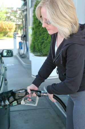 Mature female pumping her own gas. photo