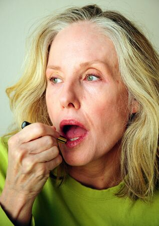Mature female beauty applying makeup to her face, Stok Fotoğraf