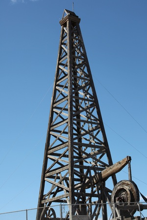 Wooden oil rig on display outdoors.