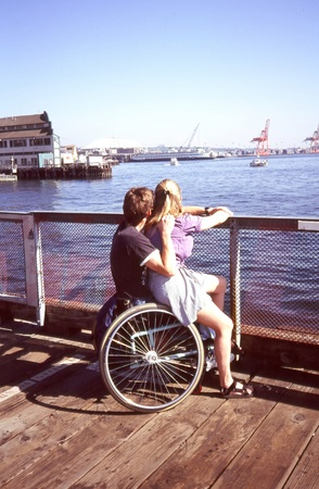 Wheelchair couple relaxing together on the pier.
