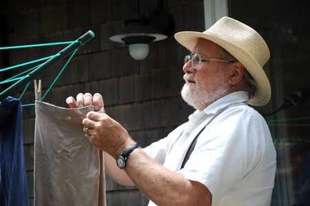 Country gentleman hanging his clothes on a line.
