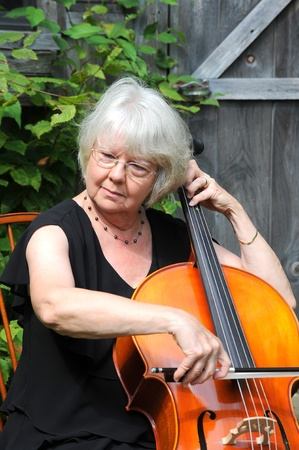 cellist: Female cellist performing outdoors.