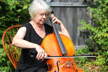 Female cellist performing on her instrument outdoors. Stock Photo