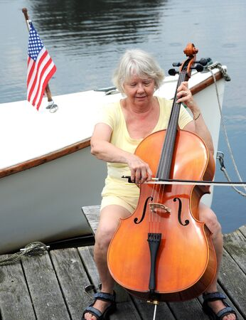cellist: Female cellist performing on the lake.