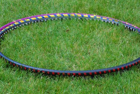 Hula hoop displayed on a lawn outside.