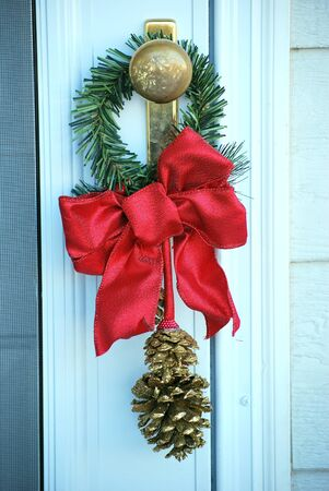 door knob: Christmas wreath on a door knob outside.