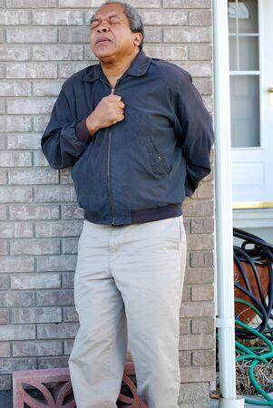 dolor de pecho: Hombre afroamericano que tiene dolores en el pecho. Foto de archivo