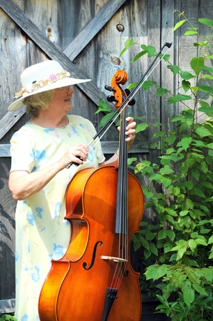 cellist: Female cellist with her instrument outdoors. Stock Photo
