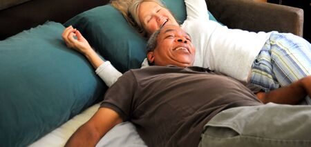 Interracial couple relaxing in bed together. photo