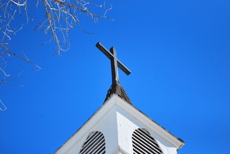 Looking up at a church steeple and cross. Stock Photo