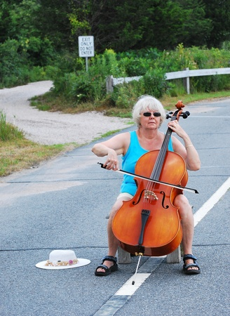 cellist: Female cellist performing in the street.