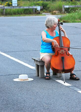 Female cellist performing in the street.