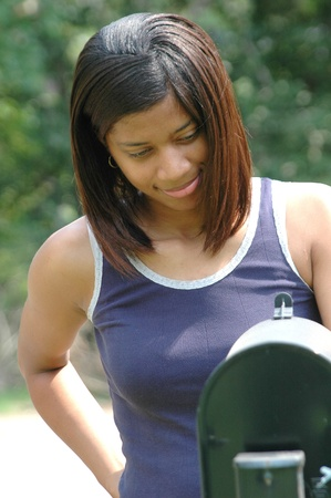 African american female checking her mailbox. photo