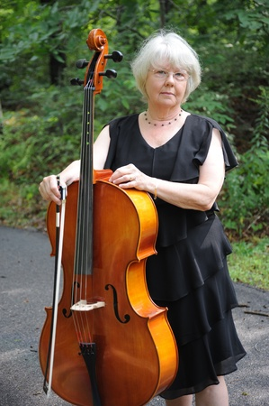 cellist: Female cellist standing outside with her cello.
