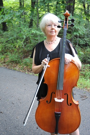 cellist: Female cellist standing outside with her instrument. Stock Photo
