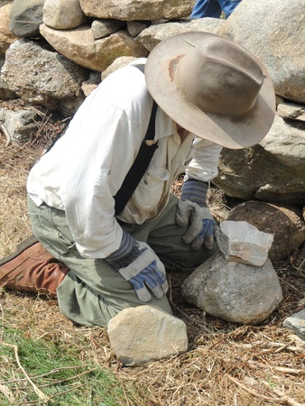 homeowner: Homeowner building a stone wall on his property