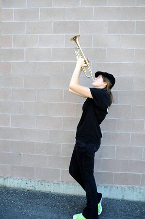 Female jazz musician blowing her trumpet