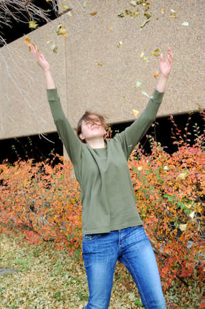 Female throwing autumn leaves in the air