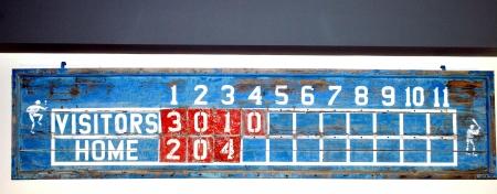 innings: Vintage baseball scoreboard displayed outdoors.