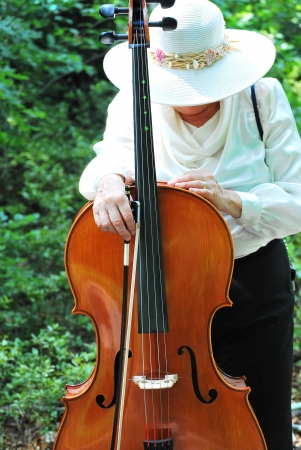 cellist: Female cellist posing with her instrument outside.