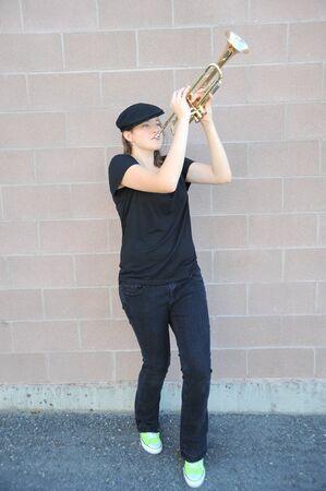 彼女の角を吹いている女性トランペット奏者 写真素材
