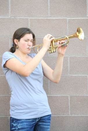 Female trumpet player blowing her horn.