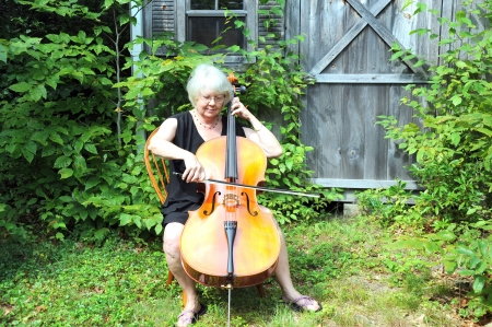 cellist: Female cellist performing outdoors