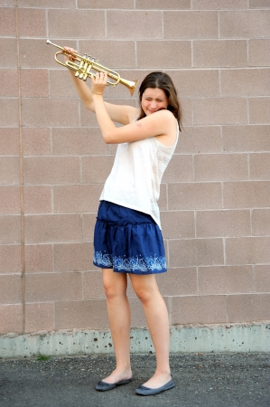 loud: Female trumpet player with her horn.