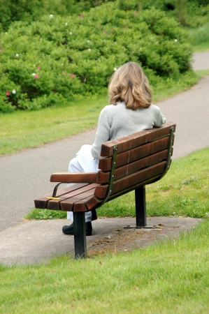 Female beauty sitting on a park bench. photo