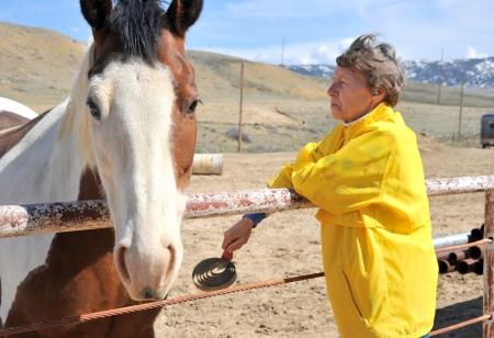 Ranchero mujer madura con su caballo fuera Foto de archivo - 19808667