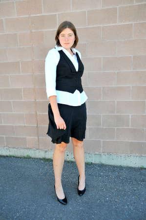 Female nanny posing against a wall outside