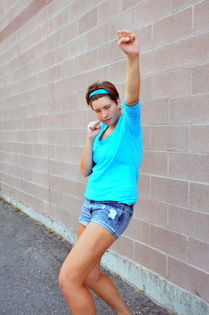 tomboy: Female tomboy posing against a wall outside  Stock Photo
