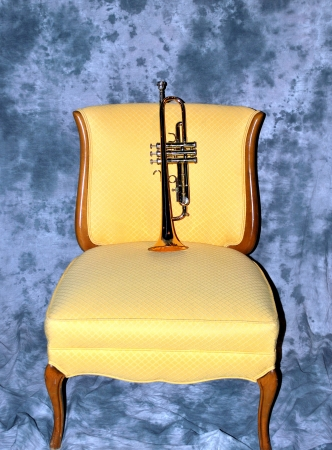 Brass trumpet on a formal yellow chair