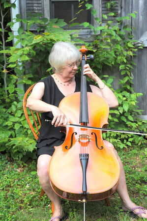 cellist: Female cellist performing on her cello outside