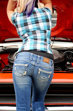 Sexy female mechanic working on her car outside. photo